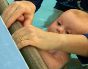 Baby holding side of pool